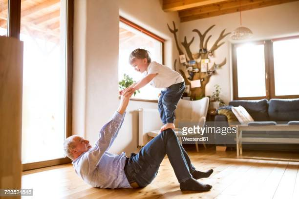 grandfather and grandson having fun at home - rough housing stock pictures, royalty-free photos & images