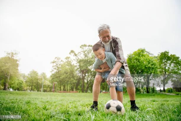 grandfather and grandson having fun, football - caneleira roupa desportiva de proteção imagens e fotografias de stock
