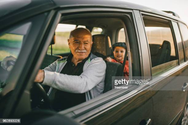 grandfather and grandson having fun on the roadtrip - family driving stock photos and pictures