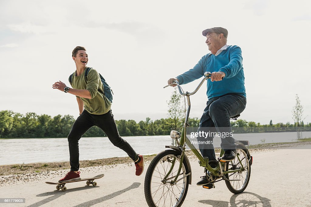 Grandfather and grandson having fun together at riverside : Stock Photo
