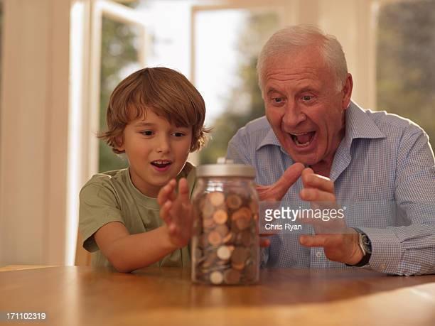 Großvater und Enkel Halten Sie im Krug jetzt voll mit Münzen