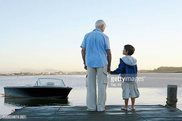 Grandfather and grandson (6-8) holding hands on jetty, rear view