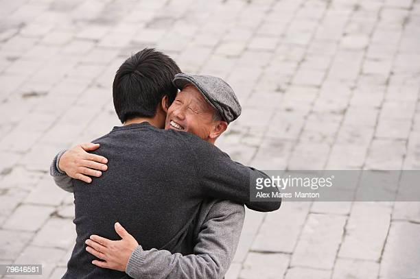 A grandfather and grandson hug each other