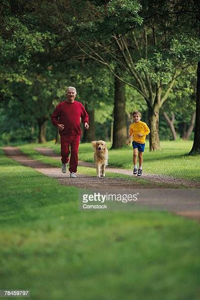 Grandfather and grandson jogging with dog