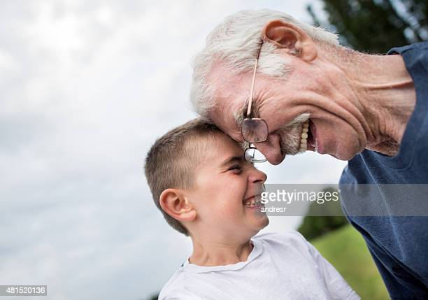 Grandfather and grandson laughing outdoors