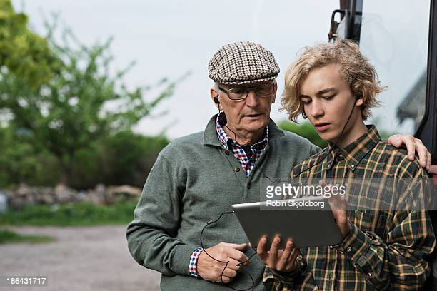 Grandfather and grandson looking at digital tablet