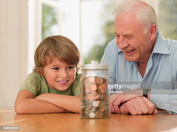 Grandfather and grandson looking at jar full of coins