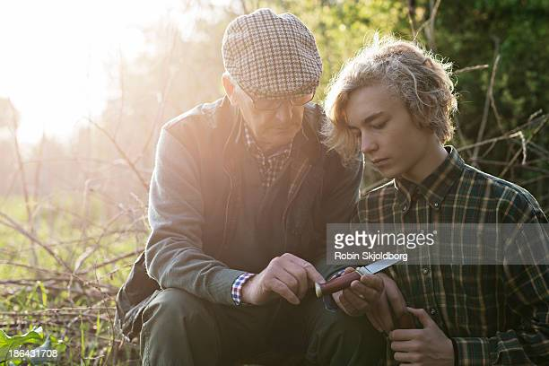 Grandfather and grandson looking at knife