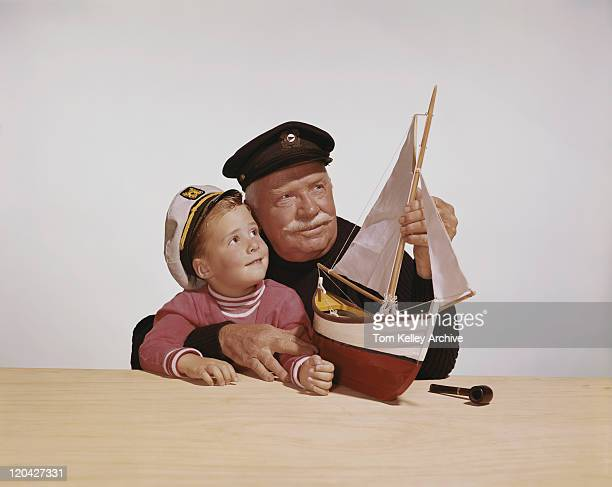 grandfather and grandson looking at ship model against white background - sailor hat stock pictures, royalty-free photos & images
