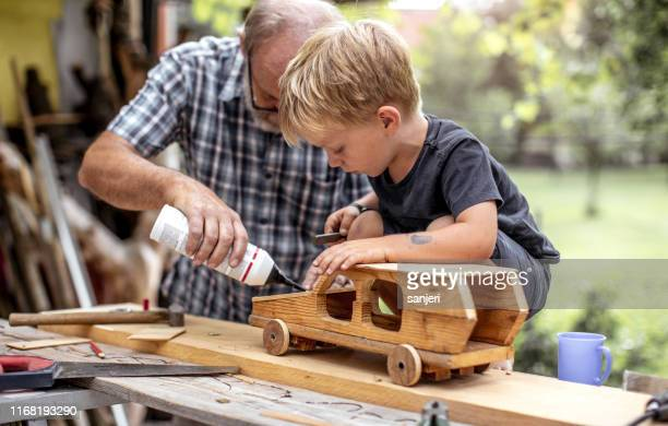 grandfather and grandson making a car from wood - model kit stock pictures, royalty-free photos & images