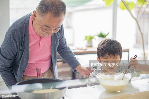 Grandfather and grandson making a hot cake at home.