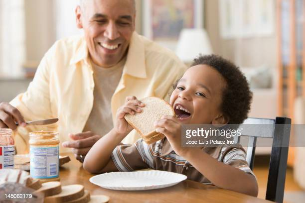 grandfather and grandson making peanut butter and jelly sandwiches - peanut butter and jelly sandwich stock pictures, royalty-free photos & images