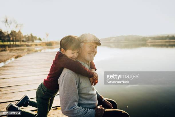 grandfather and grandson on a lake dock - grandfather stock pictures, royalty-free photos & images