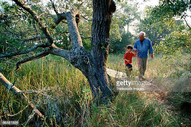 Grandfather and grandson on path through woods
