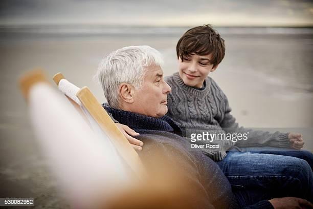 grandfather and grandson on the beach relaxing in deckchair - teenager alter stock-fotos und bilder