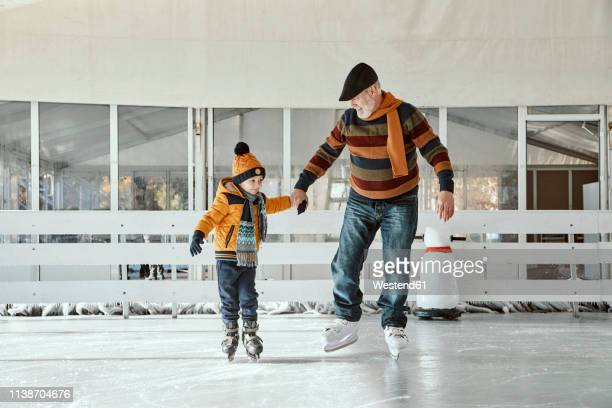 grandfather and grandson on the ice rink, ice skating - ウィンタースポーツ ストックフォトと画像