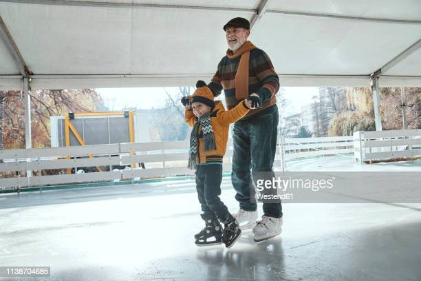 grandfather and grandson on the ice rink, ice skating - ice skating stock pictures, royalty-free photos & images