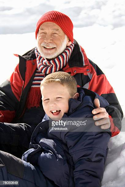 Grandfather and grandson outdoors in snow