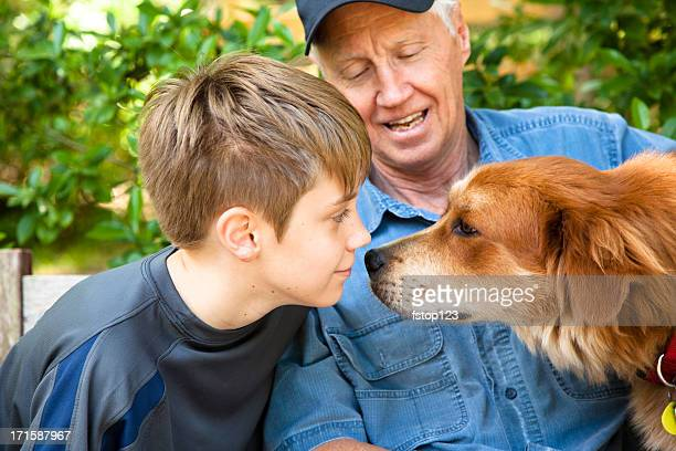 Grandfather and grandson outside with pet dog.  Golden Retriever