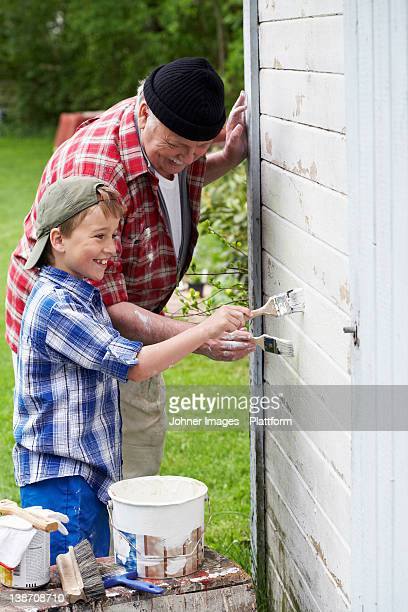 Grandfather and grandson painting their summer cottage, Sweden.