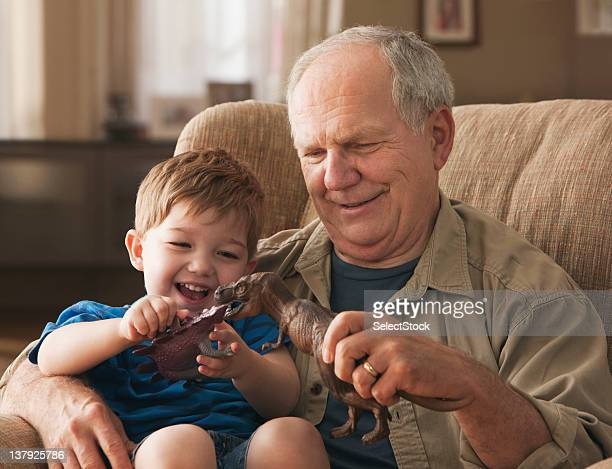 Grandfather and grandson paying with toy dinosaurs