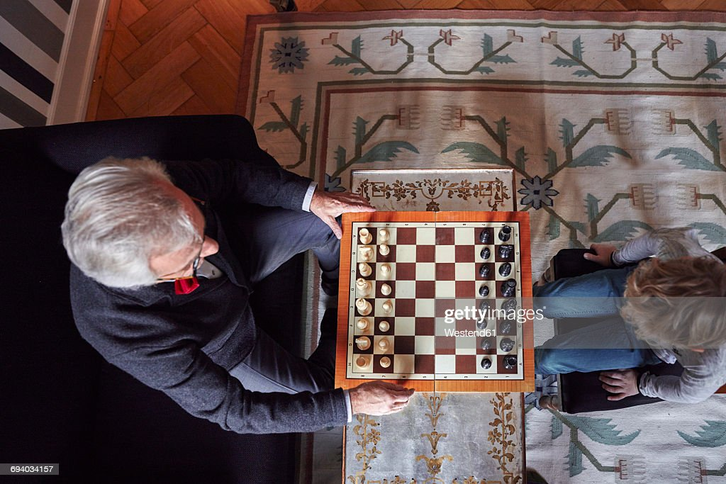 Grandfather and grandson playing chess in living room : Stock Photo