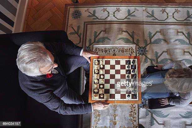 Grandfather and grandson playing chess in living room