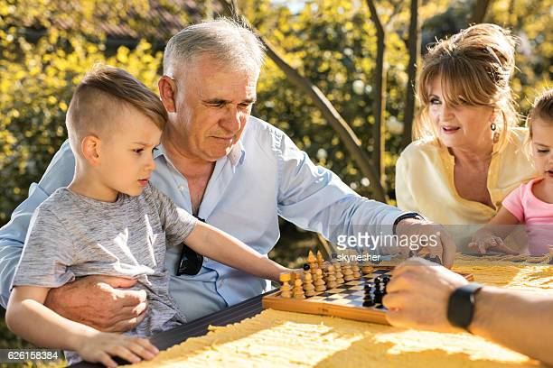 Grandfather and grandson playing chess in the backyard.