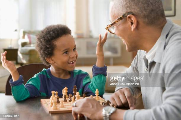 grandfather and grandson playing chess together - game board stock photos and pictures