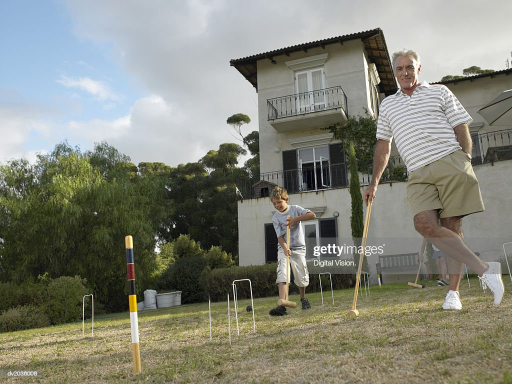 Grandfather and Grandson Playing Croquet in a Garden, Granddaughter in the Background : Stock Photo