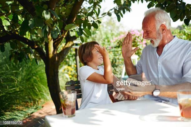 großvater und enkel spielen auf smartphone - terrassenfeld stock-fotos und bilder