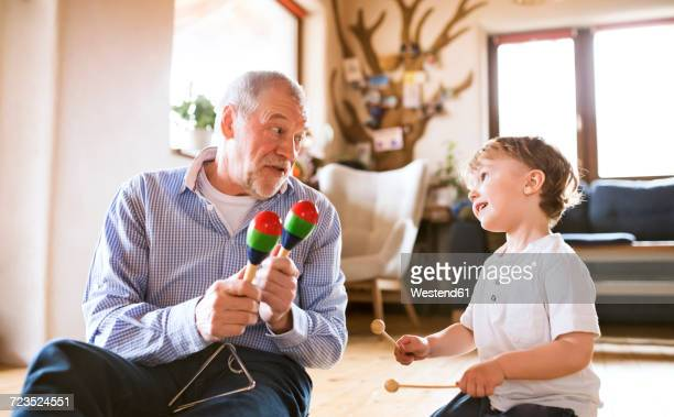 Grandfather and grandson playing music at home