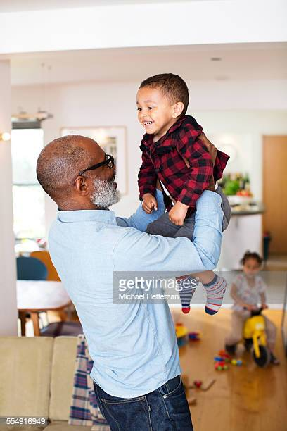 grandfather and grandson playing - maroon stock pictures, royalty-free photos & images