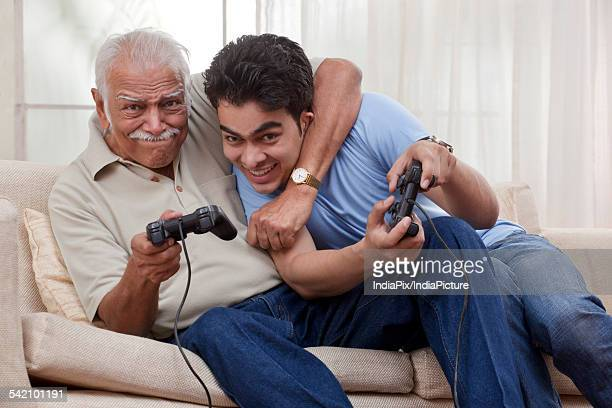 grandfather and grandson playing video game - rough housing stock photos and pictures