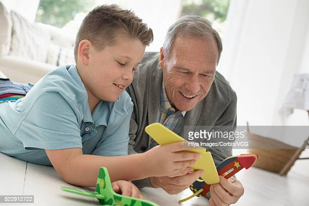 Grandfather and grandson (10-12 years) playing with model airplanes