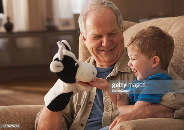 Grandfather and grandson playing with puppets