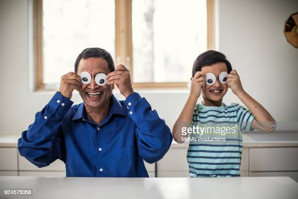 Grandfather and grandson playing with silly eyes
