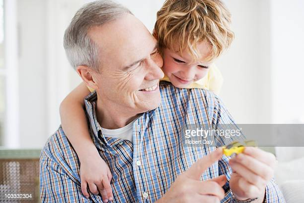 Grandfather and grandson playing with toy car