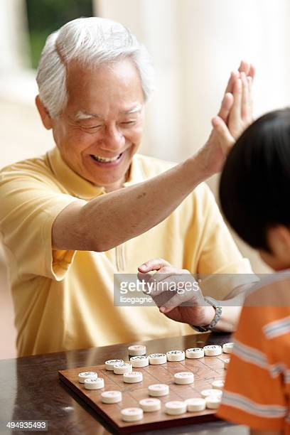 Grandfather and grandson playing Xiangqi (chinese chess)