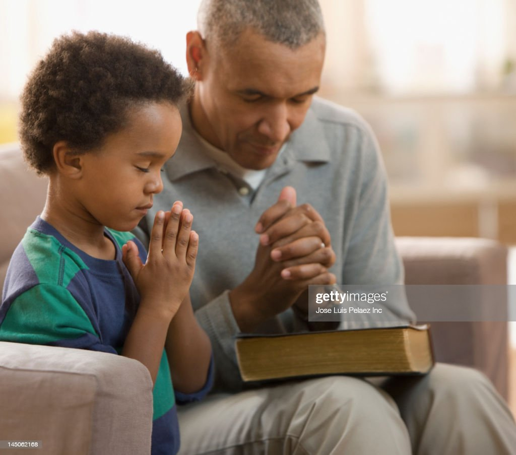 Grandfather and grandson praying together : Stock Photo