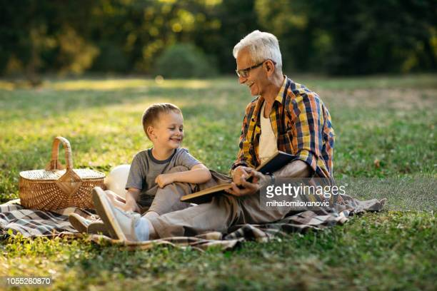 grandfather and grandson reading book - carinhoso imagens e fotografias de stock