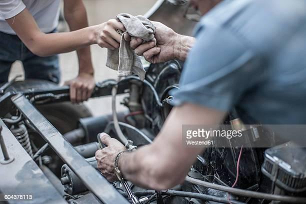 Grandfather and grandson restoring a car together