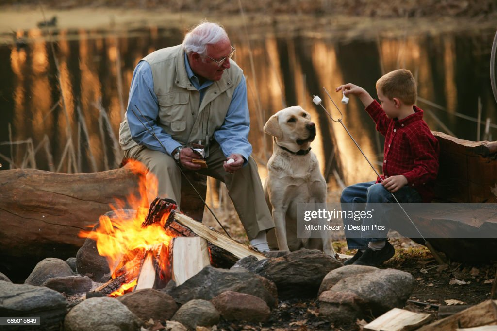 Grandfather And Grandson Roast Marshmallows On The Beach : Stock Photo