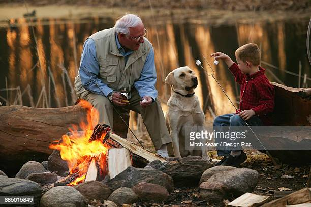 Grandfather And Grandson Roast Marshmallows On The Beach