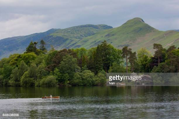 Grandfather and Grandson Rowing a Boat in Lake District Surrounding by Mountain and Lake, UK