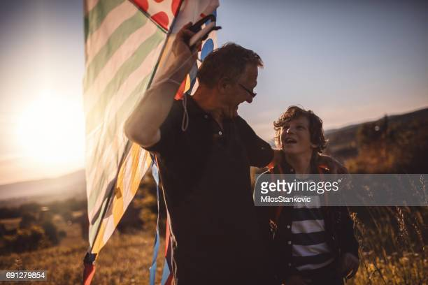 grandfather and grandson running a kite outdoors - kite toy stock pictures, royalty-free photos & images