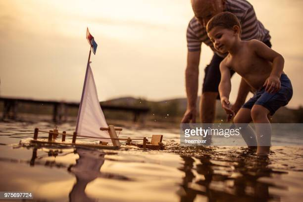 grandfather and grandson sailing the boat together - pier stock pictures, royalty-free photos & images