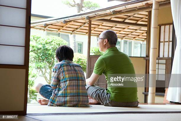 Grandfather and grandson (8-9) sitting and talking in porch, rear view