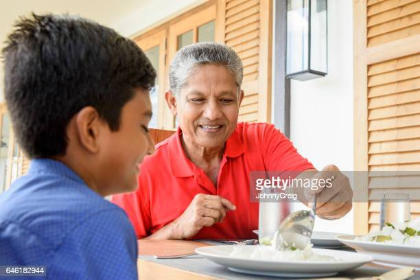 Grandfather and grandson sitting at dinner table with meal