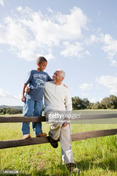 Grandfather and grandson sitting on fence